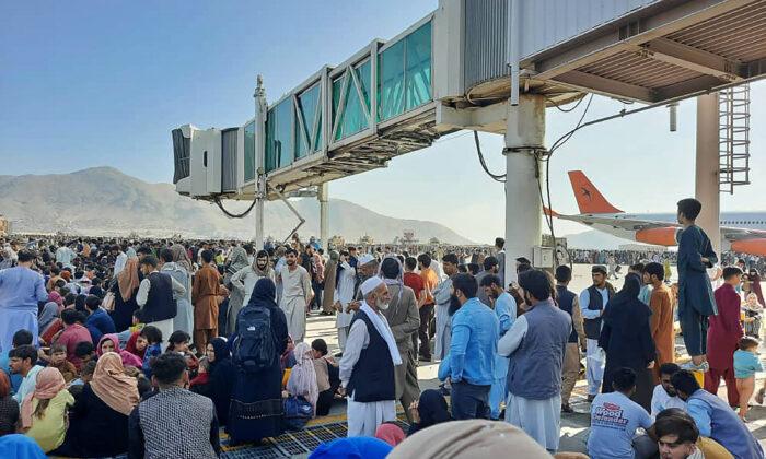 Los afganos se aglomeran en la pista del aeropuerto de Kabul mientras esperan una posibilidad de huir del control talibán en Afganistán tras el escape y abandono del país del presidente Ashraf Ghani, quien reconoció que los insurgentes habían ganado la guerra de 20 años, el 16 de agosto de 2021. (AFP vía Getty Images)