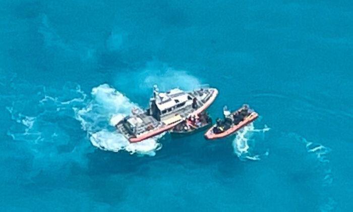 Un embarcación de la Guardia Costera de Key West intercepta una lancha de 21 pies con 22 personas a bordo, aproximadamente a 7 millas al sur de Key West, Florida, el 23 de julio de 2021. (Auxiliar de la Guardia Costera de EE.UU.)