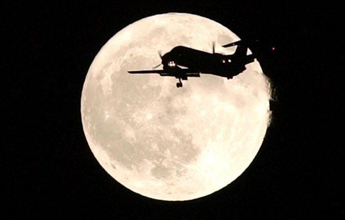 Un avión pasa frente a la luna llena mientras se acerca al Aeropuerto Internacional de San Francisco el 31 de octubre de 2001 sobre Foster City, California. La luna llena, que es una luna azul, es la primera que se produce en la noche de Halloween en 46 años. (Justin Sullivan/Getty Images)