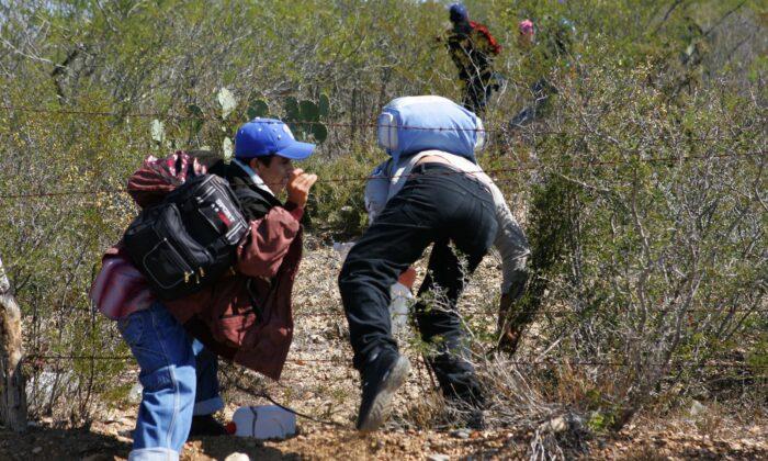 Un grupo que se dirige hacía hacía Nuevo Laredo cruza una cerca con la intención de ingresar a Estados Unidos, en una fotografía de archivo. (Omar Torres/AFP a través de Getty Images)
