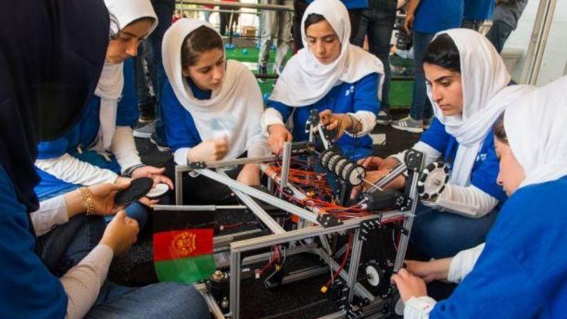 Miembros del equipo afgano de robótica femenino, con su robot cerca, observan los robots de otros países en la zona de prácticas el 17 de julio de 2017, entre las competiciones del FIRST Global Challenge 2017 en el DAR Constitution Hall, en Washington, DC. (PAUL J. RICHARDS/AFP vía Getty Images)