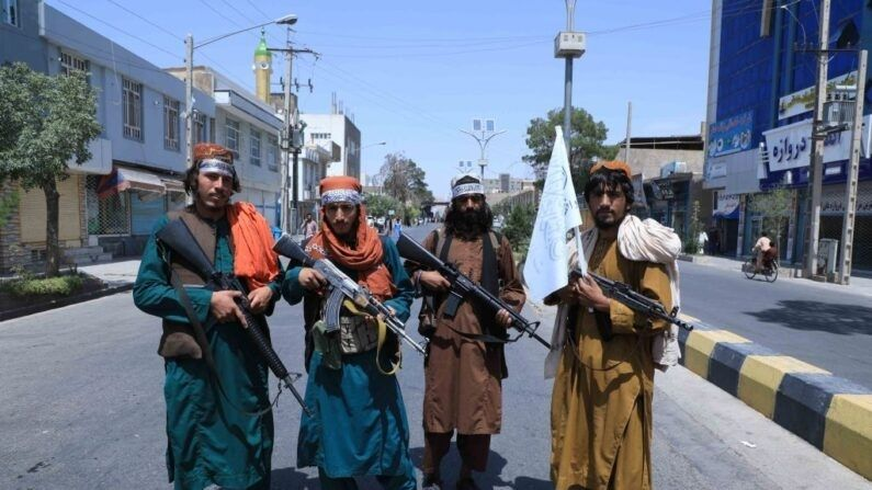 Unos terroristas talibanes montan guardia en una carretera en Herat el 19 de agosto de 2021, cerca de una procesión de Ashura que conmemora la muerte del imán Hussein, nieto del profeta Mahoma, durante la toma de control de Afganistán por parte de los terroristas. (AREF KARIMI/AFP vía Getty Images)
