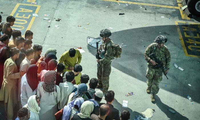 Soldados estadounidenses montan guardia mientras los afganos esperan en el aeropuerto de Kabul en Kabul, Afganistán, el 16 de agosto de 2021. (Wakil Kohsar/AFP vía Getty Images)