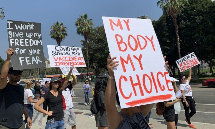 La gente sostiene carteles frente a la sede del Departamento de Policía de Los Ángeles (LAPD) para protestar contra la política del gobierno de obligar a los trabajadores de primera línea a vacunarse contra el virus del PCCh el 8 de septiembre de 2021. (Linda Jiang/The Epoch Times)