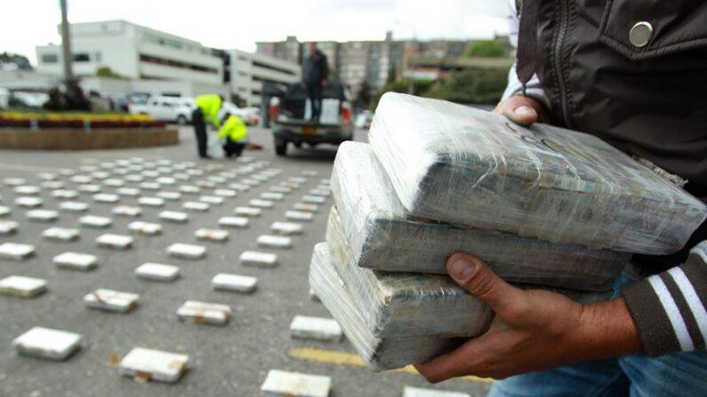 Fotografía de archivo en la que se observa a integrantes de la policía custodiando paquetes de cocaína luego de exhibirlos a los medios de comunicación. EFE/Mauricio Dueñas Castañeda