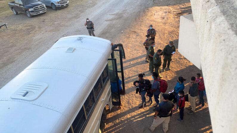 Los inmigrantes ilegales abordan un autobús para ser transportados a una estación de la Patrulla Fronteriza para su procesamiento, debajo del puente internacional, en Del Rio, Texas, el 16 de septiembre de 2021. (Charlotte Cuthbertson/The Epoch Times)