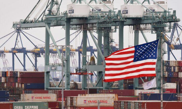 Varios contenedores marítimos chinos junto a una bandera de EE. UU. después de ser descargados en el Puerto de Los Ángeles en Long Beach (California) el 14 de mayo de 2019. (MARK RALSTON/AFP vía Getty Images)