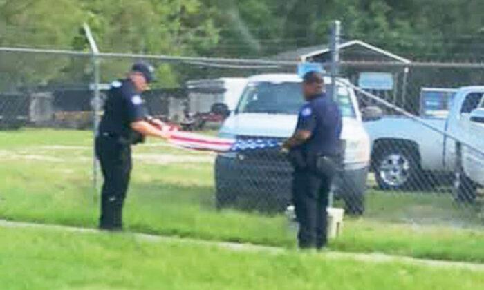 Policías muestran su patriotismo doblando una bandera que encontraron caída tras huracán Ida