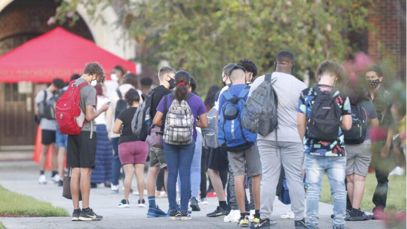 Estudiantes de secundaria esperan en la fila para que les controlen la temperatura antes de ingresar al campus en una foto de archivo. (Octavio Jones/Getty Images)
