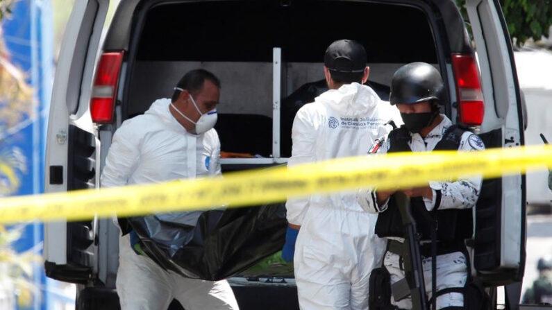 Fotografía de archivo de personal del servicio médico forense levanta los restos de varios cadáveres. EFE/ Francisco Guasco