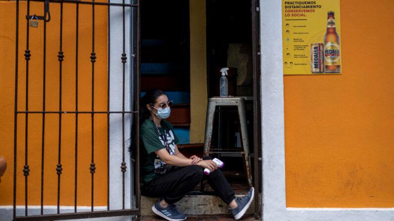 Una anfitriona de un restaurante sostiene un medidor de temperatura digital mientras espera a los clientes en la entrada de un restaurante en el Viejo San Juan (Puerto Rico), el 20 de julio de 2020. (Ricardo Arduengo/AFP vía Getty Images)
