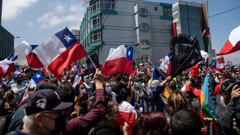 Personas agitando banderas nacionales chilenas protestan contra la migración ilegal en Iquique, Chile, el 25 de septiembre de 2021. (Martin Bernetti/AFP vía Getty Images)