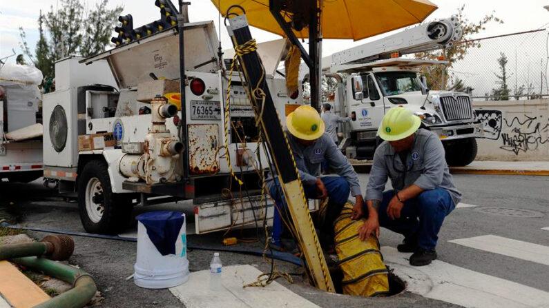 Fotografía de archivo que muestra a empleados de la Autoridad de Energía Eléctrica de Puerto Rico, Agustín Rosado (i) y Pedro Andújar (d), quienes aprovechan un apagón general para reparar una línea dañada en San Juan (Puerto Rico). EFE/Thais Llorca