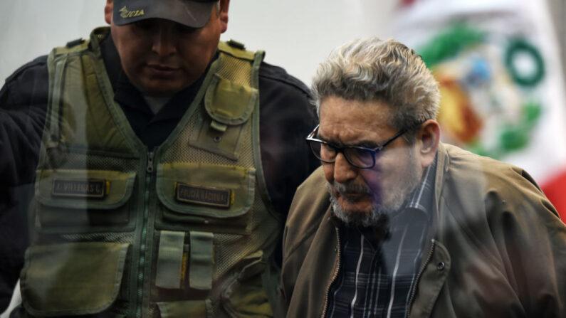 El líder del grupo terrorista Sendero Luminoso, Abimael Guzmán (d), es escoltado por un oficial de policía a su llegada a una audiencia judicial por un atentado con bomba en 1992 en Lima (Perú) que mató a 25 personas y dejó cientos de heridos, en Callao, suburbio de Lima el 11 de septiembre de 2018. (Bouroncle/AFP vía Getty Images)