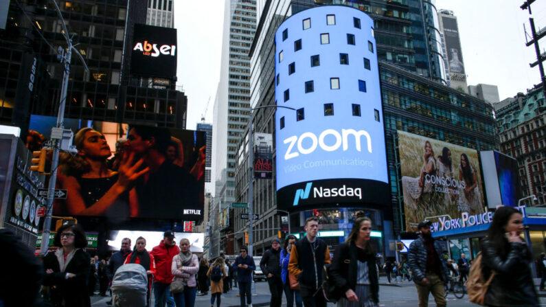 La gente pasa cerca del edificio Nasdaq mientras una pantalla muestra el logotipo de la compañía de software de videoconferencia Zoom el 18 de abril de 2019 en la ciudad de Nueva York. (Foto de Kena Betancur/Getty Images)