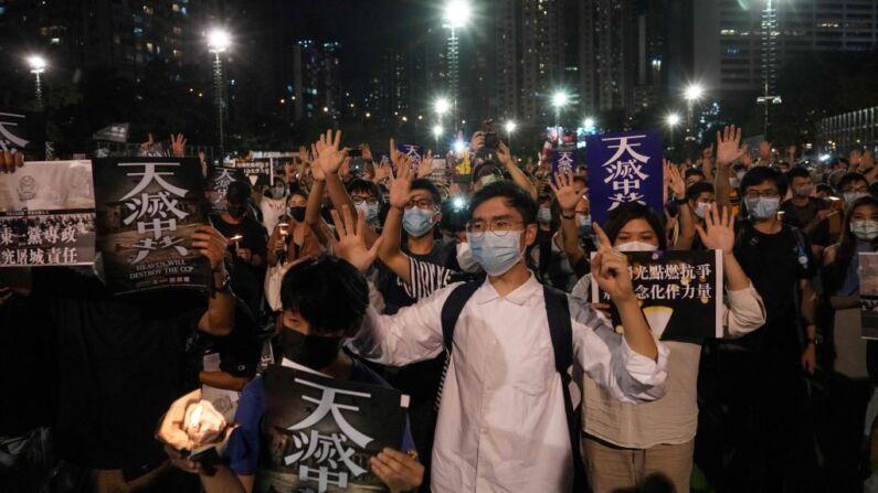 """La gente gesticula el popular lema de protesta """"Cinco demandas, ni una menos"""" mientras asiste a una vigilia en el Parque Victoria de Hong Kong el 4 de junio de 2020, después de que la conmemoración anual que tradicionalmente tiene lugar en el parque para recordar la represión de la Plaza de Tiananmen de 1989 fuera prohibida por motivos de salud pública debido a la pandemia del coronavirus COVID-19. (Foto de YAN ZHAO/AFP a través de Getty Images)"""