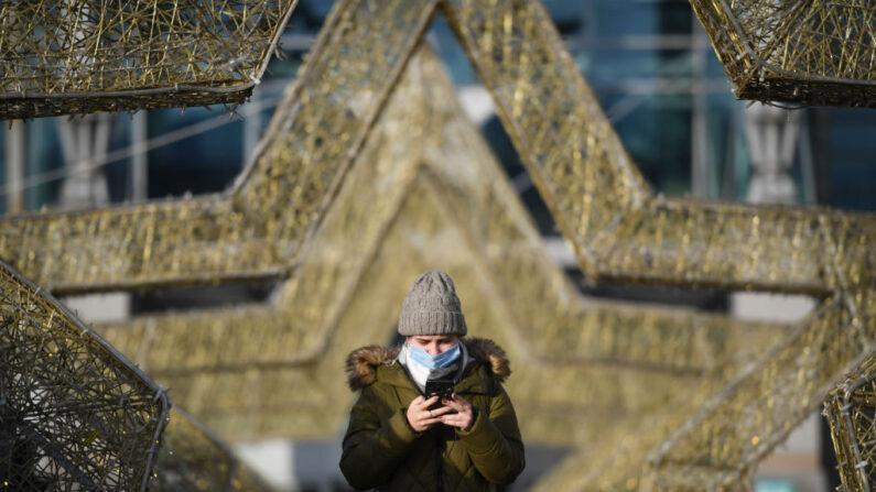 Una mujer usa su teléfono inteligente frente a un centro comercial en Moscú, el 11 de diciembre de 2020. (NATALIA KOLESNIKOVA/AFP a través de Getty Images)