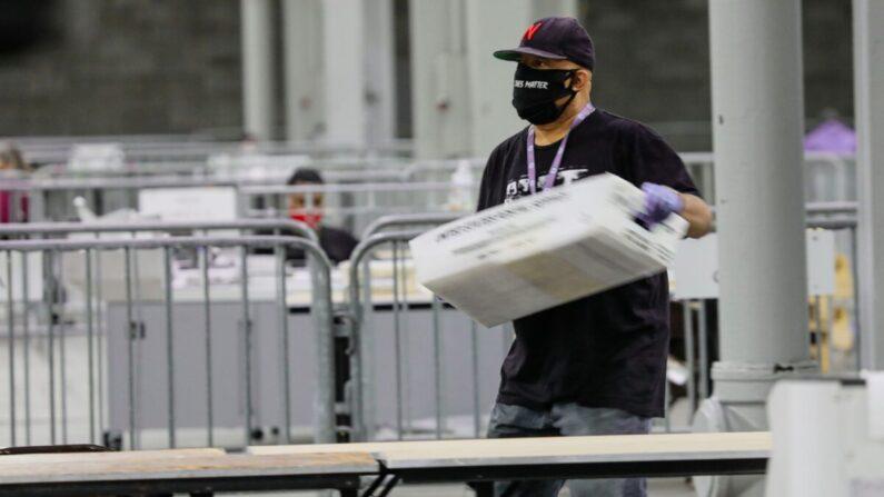 Durante las elecciones de segunda vuelta del Senado de Georgia, un trabajador lleva un contenedor de boletas para escanear en el Centro de Congresos Mundial de Georgia en Atlanta, Georgia, el 5 de enero de 2021. (Sandy Huffaker/AFP a través de Getty Images)