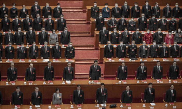 El líder chino Xi Jinping (en el centro) y los legisladores cantan el himno durante la sesión de clausura de la conferencia de la legislatura títere, en el Gran Salón del Pueblo, en Beijing, China, el 11 de marzo de 2021. (Kevin Frayer/Getty Images)