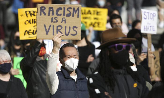 """Un hombre sostiene un cartel que dice """"El racismo es un virus"""" durante la manifestación """"No somos silenciosos"""" en contra del odio hacia los asiáticos en respuesta al reciente crimen contra los asiáticos en el distrito internacional de Chinatown de Seattle, Washington, el 13 de marzo de 2021. (Jason Redmond/AFP a través de Getty Images)"""
