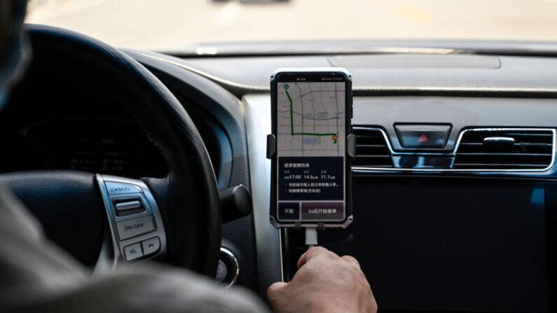 Un conductor usa la app china Didi en su smartphone mientras conduce por una calle en Beijing el 2 de julio de 2021. (Jade GAO/AFP a través de Getty Images)