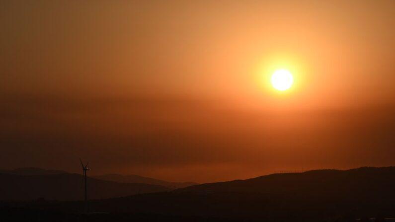 El sol se pone cerca de un molino de viento en Palmdale, California, donde las temperaturas alcanzaron los 106 grados Fahrenheit el 12 de julio de 2021. (ROBYN BECK/AFP vía Getty Images)