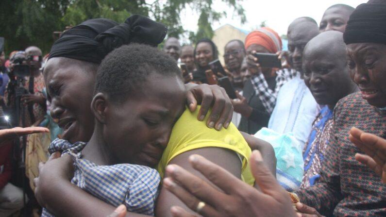 Una madre abraza a su hija el 25 de julio de 2021 después de que fuera liberada junto con otros 27 estudiantes de la escuela secundaria Bethel Baptist. Hombres armados secuestraron a 121 estudiantes en un instituto del noroeste de Nigeria a principios de julio.  (AFP vía Getty Images)