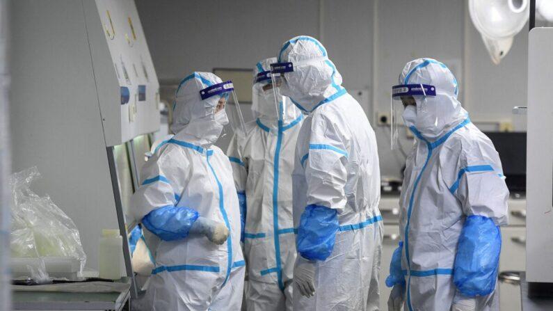 Técnicos de laboratorio con equipo de protección personal (EPP) trabajan con muestras que se someterán a pruebas de COVID-19 en el laboratorio Fire Eye, una instalación de pruebas de COVID-19, en Wuhan, en la provincia central china de Hubei, el 4 de agosto de 2021. (STR/AFP vía Getty Images)