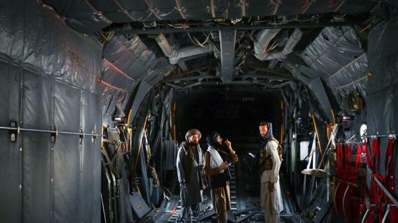 Combatientes talibanes en el interior de un avión de la Fuerza Aérea Afgana en el aeropuerto de Kabul el 31 de agosto de 2021, después de que Estados Unidos retiró todas sus tropas. (WAKIL KOHSAR/AFP vía Getty Images)