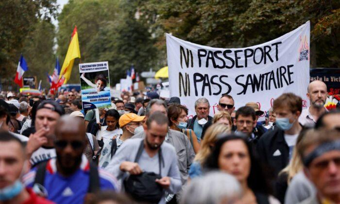"""Los manifestantes marchan durante una protesta contra los pasaportes de vacunación pandémica, en la Avenida De Villiers, en París, el 11 de septiembre de 2021. El letrero dice """"Ni pasaporte ni pase de salud"""". (Thomas Samson/AFP a través de Getty Images)"""