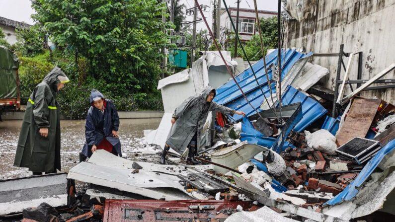 Rescatistas limpian los escombros después que un sismo de magnitud 5.4 causó la muerte a tres personas y dejó una docena de heridos en Luzhou, en la provincia suroccidental china de Sichuan, el 16 de septiembre de 2021. (STR/AFP vía Getty Images)