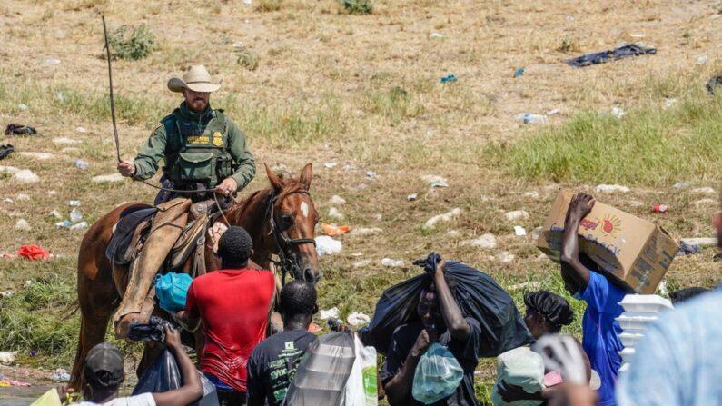 Un agente de la Patrulla Fronteriza de los Estados Unidos mueve las riendas de su caballo mientras intenta evitar que los migrantes haitianos ingresen al territorio estadounidense a orillas del río Grande cerca del Puente Internacional Acuña del Río en Del Río (Texas) el 19 de septiembre de 2021. (Paul Ratje / AFP a través de Getty Images)