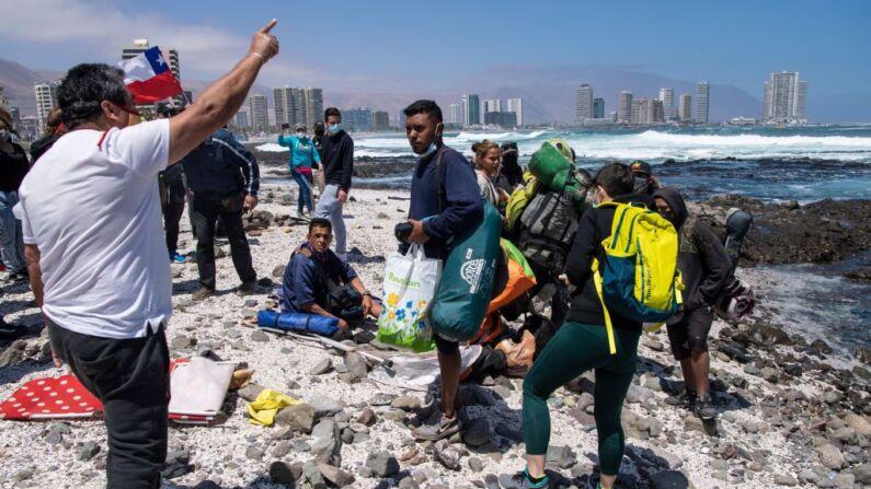 Migrantes venezolanos son asediados por manifestantes durante una marcha de protesta contra la migración ilegal en Iquique, Chile, el 25 de septiembre de 2021. (Martin BernettiI/AFP a través de Getty Images)