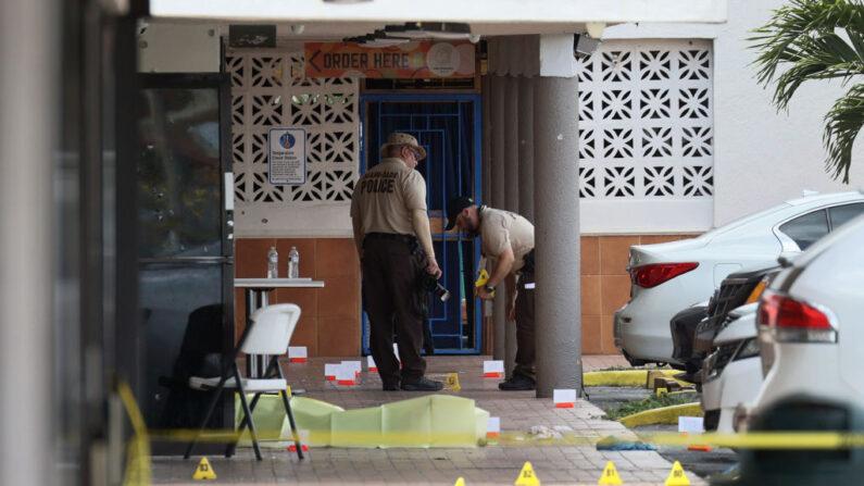 La policía de Miami-Dade investiga cerca de los marcadores de evidencia de casquillos en el suelo donde tuvo lugar un tiroteo masivo fuera de un salón de banquetes el 30 de mayo de 2021 en Hialeah, Florida. (Joe Raedle/Getty Images)