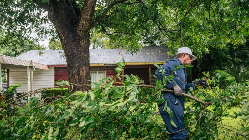 Dallas Baines, de 77 años, se deshace de las ramas de los árboles caídos tras el paso de la tormenta tropical Nicholas por la zona el 14 de septiembre de 2021 en Houston, Texas. (Brandon Bell/Getty Images)