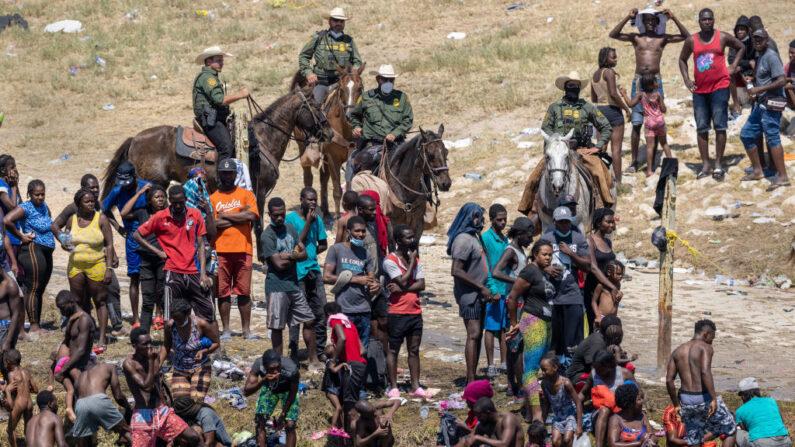Agentes de la Patrulla Fronteriza de Estados Unidos observan a los inmigrantes haitianos en la orilla del Río Grande en Del Río, Texas, el 20 de septiembre de 2021, visto desde Ciudad Acuña, México. (John Moore/Getty Images)