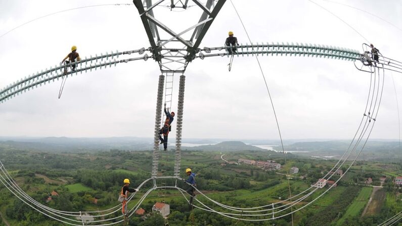 Electricistas trabajan en los cables de una torre de transmisión de más de 110 metros de altura el 9 de julio de 2015 en el condado de Lai'an, ciudad de Chuzhou, provincia china de Anhui. (VCG/VCG vía Getty Images)