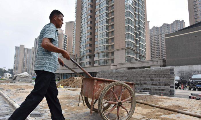 Un trabajador empuja un carro en el sitio de construcción de un complejo de viviendas, en Beijing, el 15 de agosto de 2017. (Greg Baker/AFP/Getty Images)