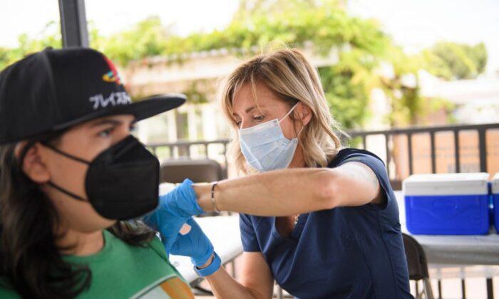 Una enfermera administra una dosis de la vacuna anti-COVID de Pfizer a una estudiante de secundaria, en el campus de la Universidad Estatal de California, en Long Beach, California, el 11 de agosto de 2021. (Patrick T. Fallon/AFP a través de Getty Images)