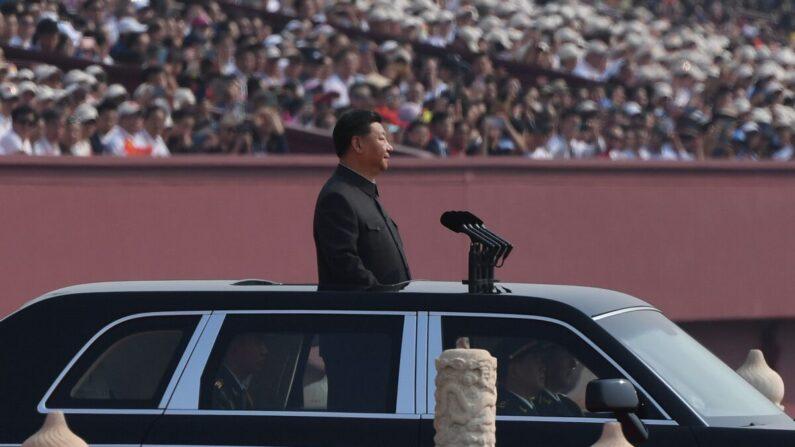 El líder del régimen chino, Xi Jinping, comienza a pasar revista a las tropas desde un auto durante un desfile militar en la plaza de Tiananmen, en Beijing, el 1 de octubre de 2019. (Greg Baker/AFP/Getty Images)