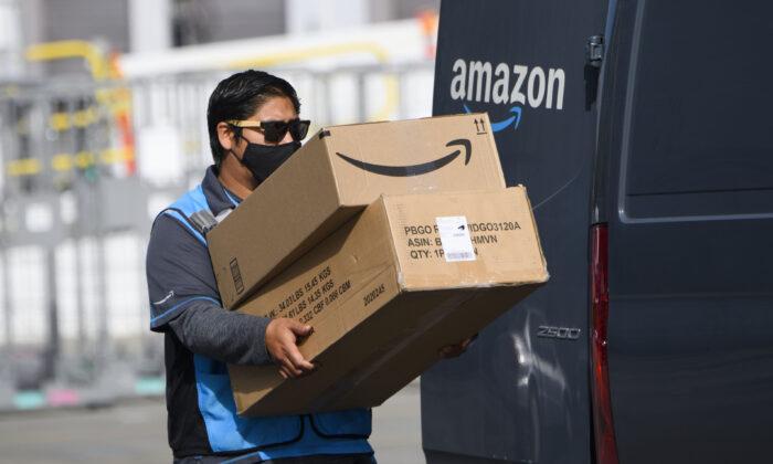 Un conductor de reparto de Amazon.com Inc. lleva cajas a una furgoneta fuera de una instalación de distribución el 2 de febrero de 2021 en Hawthorne, California. (Patrick T. Fallon/AFP vía Getty Images)