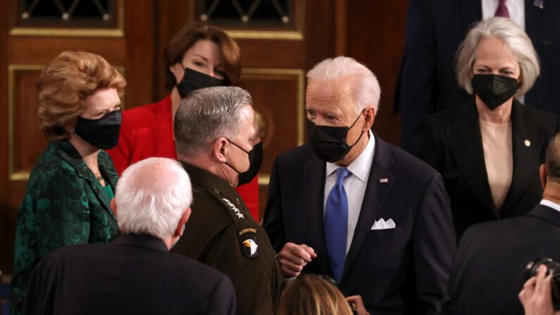 El presidente Joe Biden habla con el presidente del Estado Mayor Conjunto Mark A. Milley (izq.) tras dirigirse a una sesión conjunta del Congreso en el Capitolio de los Estados Unidos en Washington el 28 de abril de 2021. (Chip Somodevilla/Getty Images)