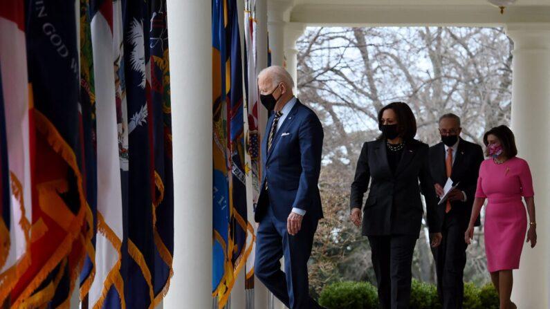 El presidente Joe Biden, con (I-D) la vicepresidenta Kamala Harris, el líder de la mayoría del Senado Chuck Schumer (D-NY), y la presidenta de la Cámara de Representantes Nancy Pelosi (D-Calif.), llegan para hablar sobre el Plan de Rescate Estadounidense en el Jardín de Rosas de la Casa Blanca en Washington, el 12 de marzo de 2021. (Olivier Douliery/AFP vía Getty Images)