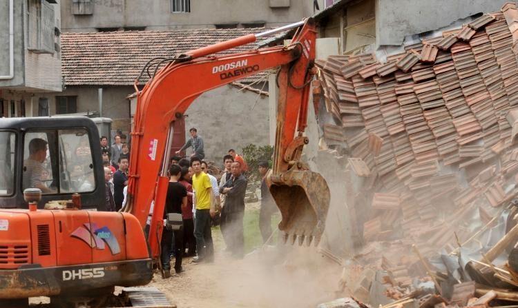 Las autoridades chinas derriban casas que, según el gobierno local, son ilegales en Wuhan, provincia central china de Hubei, el 7 de mayo de 2010. (STR/AFP/Getty Images))
