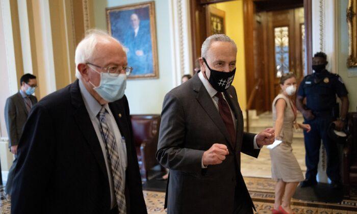 El senador Bernie Sanders (I-Vt.) camina con el líder de la mayoría del Senado, Chuck Schumer (D-N.Y.), el 11 de agosto de 2021, después de una reunión presupuestaría sobre un proyecto de ley de 3,5 billones de dólares que fue aprobado por los demócratas del Senado, el 9 de agosto, en Washington. (Win McNamee/Getty Images)