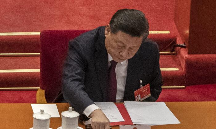 El líder de China, Xi Jinping, presiona un botón para votar a favor de una resolución para revisar el sistema electoral de Hong Kong en el Gran Salón del Pueblo en Beijing, el 11 de marzo de 2021. (Kevin Frayer/Getty Images)