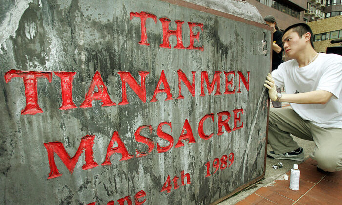 """Un estudiante de la Universidad de Hong Kong limpia una placa el 4 de mayo de 2005, debajo de """"La Columna de la Vergüenza"""", un monumento construido para honrar a los muertos y avergonzar al Partido Comunista Chino, que se negó a pedir disculpas por la masacre de la Plaza de Tiananmen, la matanza de estudiantes que tuvo lugar el 4 de junio de 1989 en la Plaza de Tiananmen de Beijing. (MIKE CLARKE/AFP vía Getty Images)"""