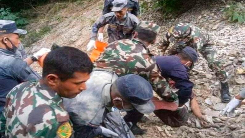 Una foto facilitada por el ejército nepalí muestra a los trabajadores de rescate y a la población local alineando los cuerpos de las víctimas en el lugar del accidente de un autobús de pasajeros en el distrito de Mugu, Nepal, el 12 de octubre de 2021. EFE-EPA/Ejército Nepalí