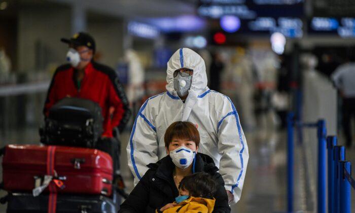 Pasajeros cubiertos con mascarillas llegan al aeropuerto internacional de Shanghái Pudong en Shanghái el 19 de marzo de 2020. (Hector Retamal/AFP vía Getty Images)