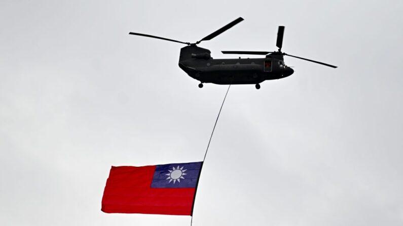 Un helicóptero militar vuela con la bandera nacional de Taiwán durante el Día Nacional frente a la Oficina Presidencial en Taipei el 10 de octubre de 2020. (SAM YEH/AFP vía Getty Images)